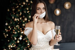 Woman in dress with mask and champagne near New Year decorations