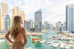 Woman in Dubai Marina, United Arab Emirates. Attractive lady wearing a long dress admiring Marina harbor daylight view