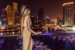 woman in Dubai, United Arab Emirates. Attractive lady wearing a long dress. Girl admiring Dubai Marina at night