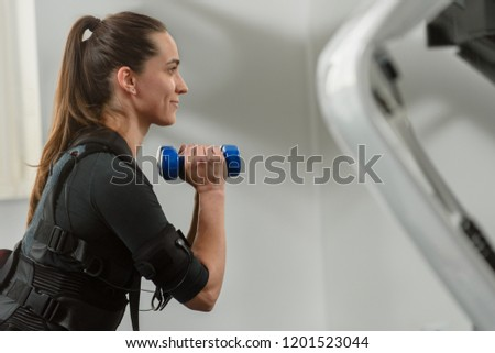 Woman in electro muscular stimulation suit training with dumbbells #1201523044