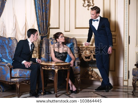 Woman in evening dress and young man in suit sitting in the armchairs and conversing with another man