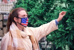 Woman in face medical mask with usa flag chooses a christmas tree. Lifestyle, a celebration of the coronavirus pandemic