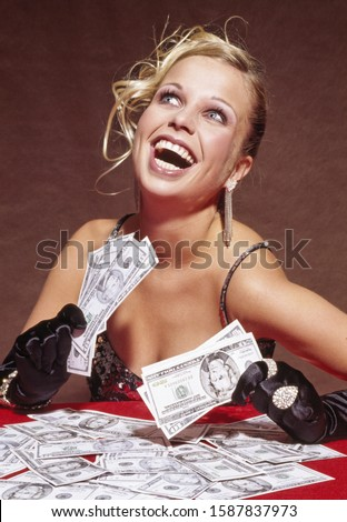 Woman in fancy clothing with pile of US Dollars