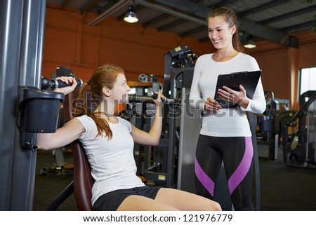 Woman in fitness center on a shoulder press listening to female trainer