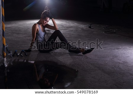Woman in Fitness Suit do heavy exercise, training at crossfit Garage tool, dark shadow studio lighting, give up no more fight