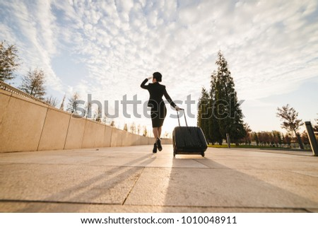 woman in flight stewardess carries a large suitcase #1010048911