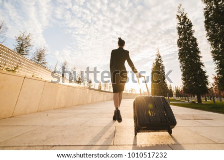 woman in flight stewardess carries a large suitcase #1010517232