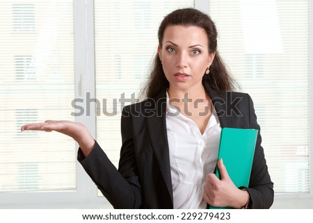 Woman in formal clothes holding empty hand like holding something
