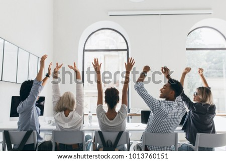 Woman in formal shirt with blonde hair waving hands, sitting between coworkers in big light conference hall. Photo from back of tired managers stretching during meeting in office.