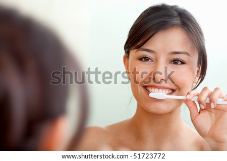 Woman in front of a mirror brushing her teeth #51723772