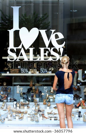 Woman in front of a shop Window With Sale Banners. Shopping Series.