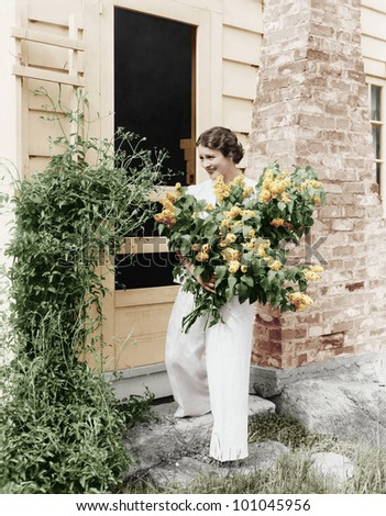 Woman in front of her house gathering flowers in her arms