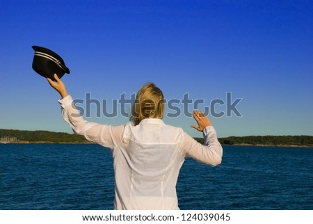 woman in front of the sea, waving to say goodbye