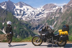 Woman in full biker outfit, jacket protection turtle. Touring motorcycle with big bags. The snowy peaks of the Alpine mountains on background. Grossglockner Pass Hochalpenstrasse. Austria, Italy