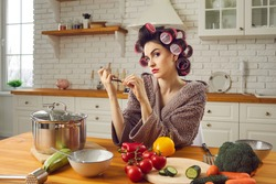 Woman in funny curlers sitting at kitchen table and filing nails with thoughtful face expression. Angry wife waiting for husband from work. Young housewife cooking, thinking and making cunning plans