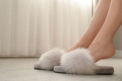 Woman in fuzzy slippers at home, closeup. Space for text