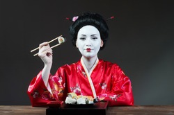 Woman in geisha makeup eating sushi, gray background