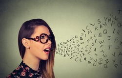 Woman in glasses talking with alphabet letters coming out of her mouth. Communication, information, intelligence concept