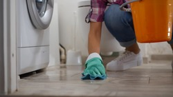 Woman in gloves having leaking washing machine wiping floor and wrinkling rag in bucket. Housewife near broken washing machine collecting water in basin in bathroom