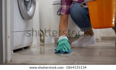 Woman in gloves having leaking washing machine wiping floor and wrinkling rag in bucket. Housewife near broken washing machine collecting water in basin in bathroom