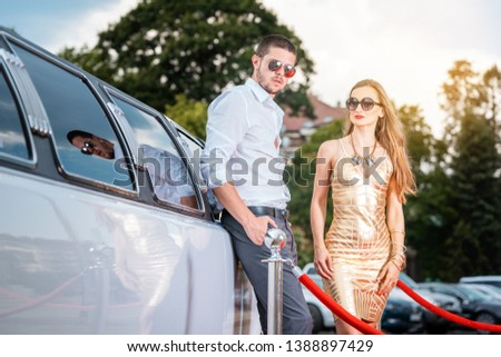Woman in golden dress and man leaning against a limo car