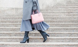 Woman in gray boots and a pink bag. Girl on the stairs. close-up.