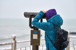 Woman in green down jacket looking at sea through coin-operated binocular viewer in winter. Tourism and sightseeing concept.