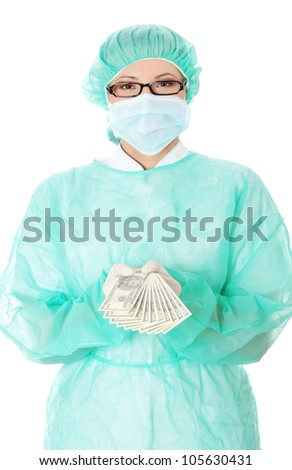 Woman in green medical uniform is standing and holding dollar bills. Isolated on the white background.