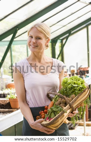 Woman in greenhouse holding basket of vegetables smiling