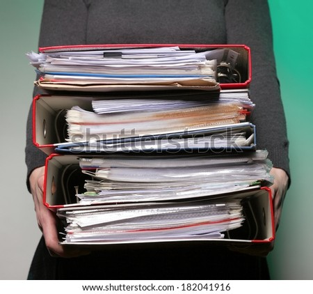 woman in grey holding stack of folders. Pile with old documents and bills on green background