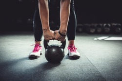 Woman in gym holding a kettlebell. Working Out
