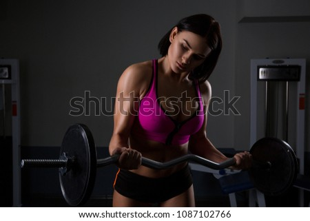 Woman in gym lifting weights. The athlete lifts the vulture or dumbbell
