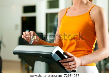 Woman in gym or health club reading her training plan which is stored on a modern key system