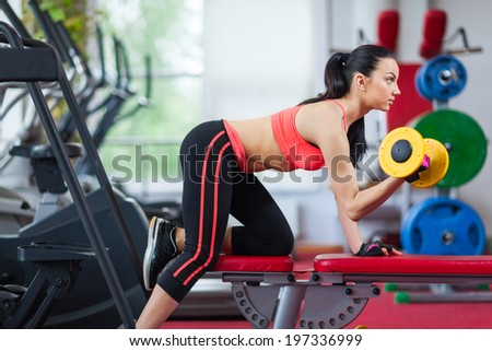 Woman in gym sport exercising with dumbbells lifting weights, young girl working out on her biceps