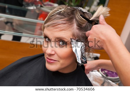 woman in hairdresser salon on preparation for hair coloring