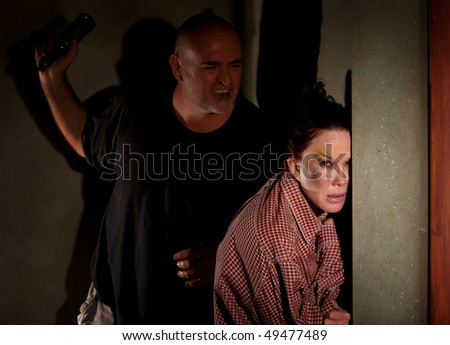 Woman in hallway with bruise on her cheek with menacing man