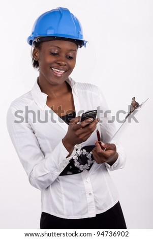 Woman in hard-hat with notepad sending a text message.