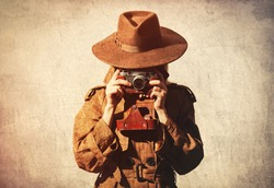 Woman in hat and cloak as a spy with camera on gray background.
