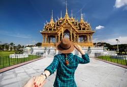 Woman in hat and green checked shirt leading man to the Ananta Samakhom Throne Hall in Thai Royal Dusit Palace, Bangkok, Thailand