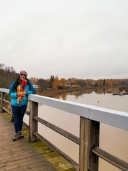 Woman in hat and scarf on a bridge next to the canal in Porvoo