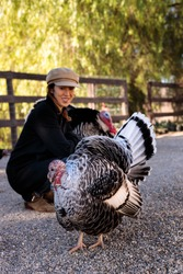 Woman in hat crouched down between two large male turkeys