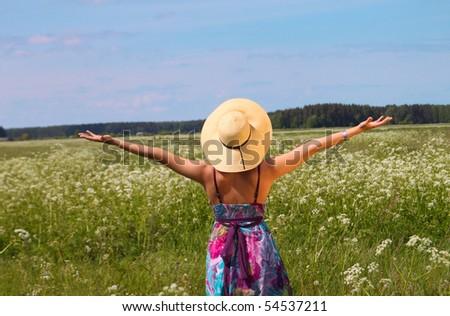 woman in hat enjoying nature in a green field