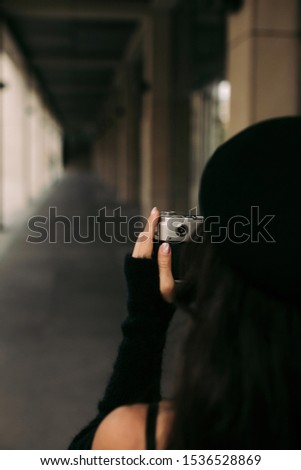 woman in hat holding retro camera. Photographer making pictures