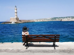 Woman in hat is sitting on a bench on  the sea coast with beautiful view on lighthouse during summer holidays. Architecture on Crete in Chania. Travel and relax.