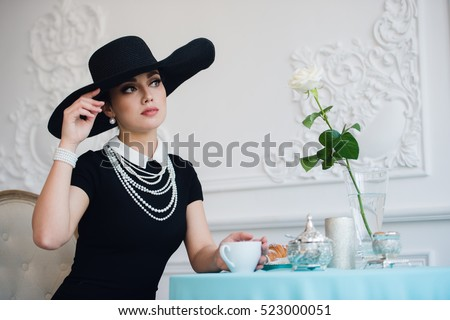 Woman in hat, much like the famous actress, croissant eating and drinking tea. #523000051