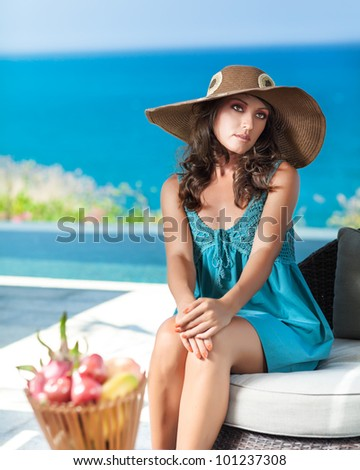Woman in hat near the pool - stock photo