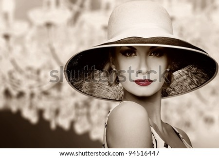 Woman in hat on vintage crystal lamp background.