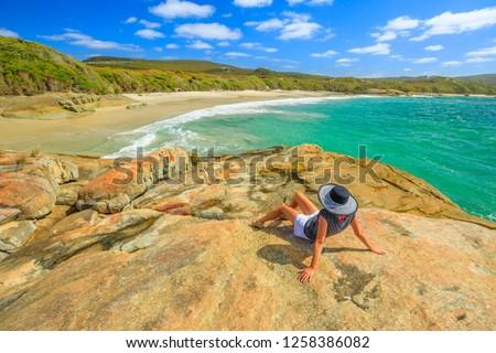 Woman in hat sunbathing on the rocks of Waterfall beach in Denmark, Western Australia. Caucasian tourist looking Great Southern Ocean in William Bay NP. Summer destination in Australia.