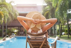 woman in hat taking sunbath near swimming pool