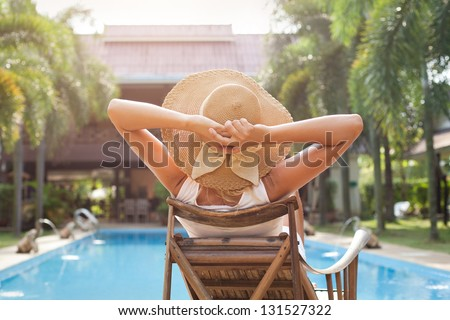 woman in hat taking sunbath near swimming pool